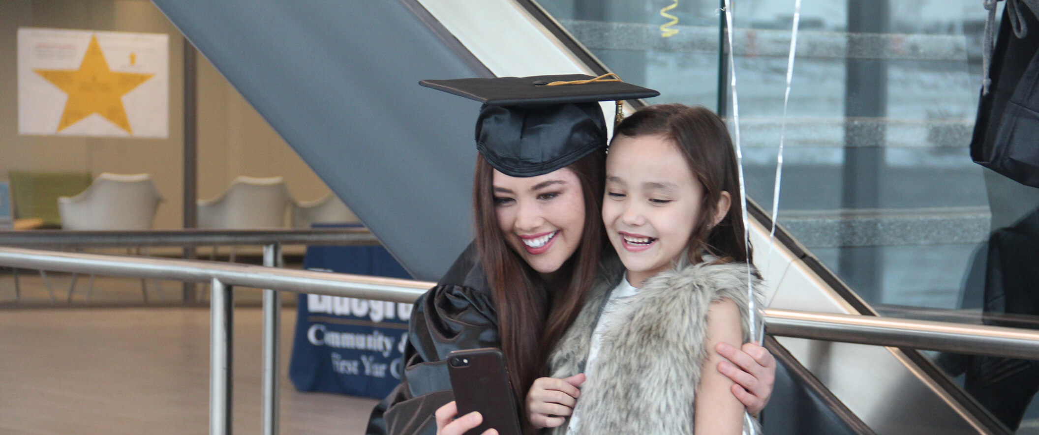 mom in grad outfit taking selfie with daughter