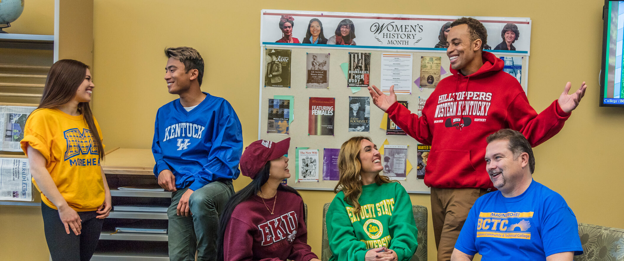 students in lounge wearing different college sweatshirts