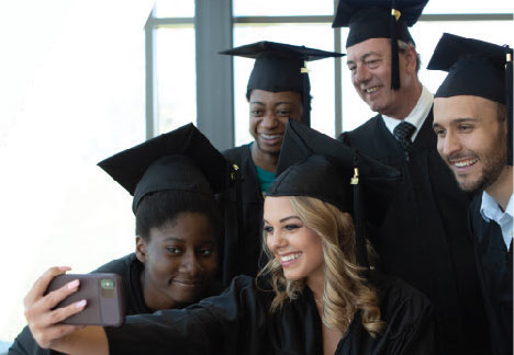 photo of a group of students in their caps and gowns taking a selfie