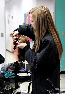 Student practicing hair dressing on manaquin