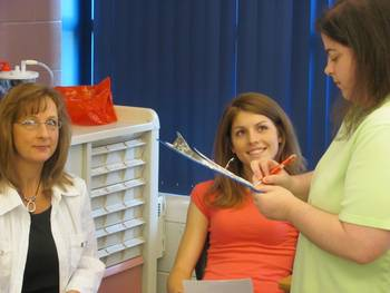 photo of an instructor and 2 students in a clinical environment