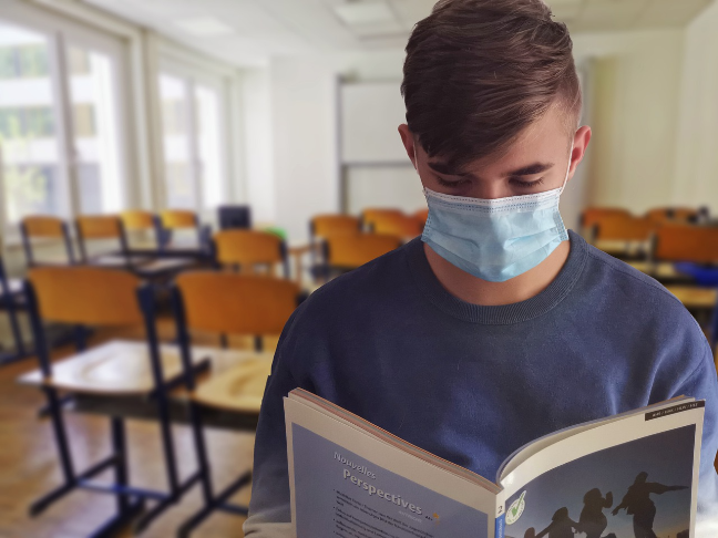 male student reading while wearing mask