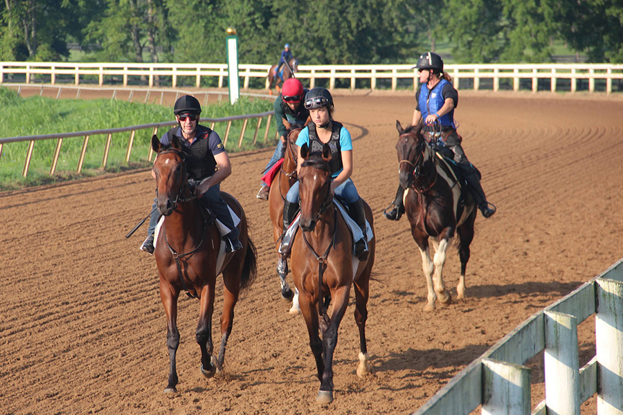 Equine Students riding horseback on a track