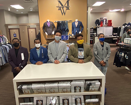 Members of a Few Good Men standing together in Men's Warehouse with new suits