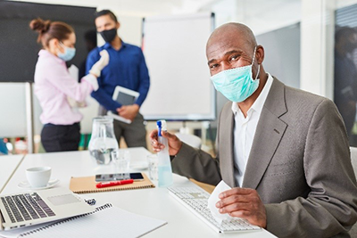 Employee in facemask cleaning their workspace