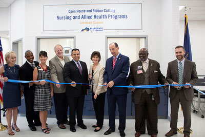 Dr. Julian standing with other officials and cutting the ribbon at the Leestown open house