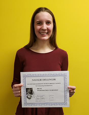 Natalie Dellinger holding a certificate of recognition for BIO 112 Introduction to Biology